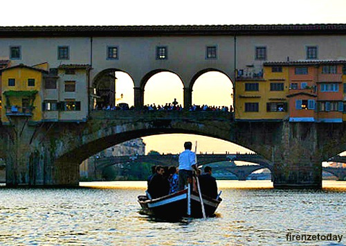 A traditional Florentine boat, called 'barchetto', goes under the Ponte Vecchio at dusk