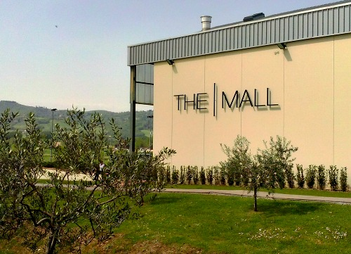 Exterior of The Mall, surrounded by rolling hills and olive trees
