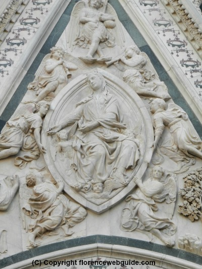 The almond shaped oval which gives the door its name, with the relief with image of Mary ascending to the heavens