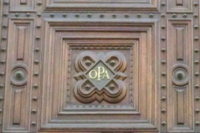 The wooden part of the door with the letters OPA, the organization that oversees the Duomo