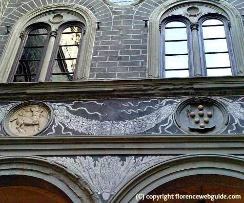Michelozzo courtyard detail: painted frieze, medallions of mythological scenes, and the Medici family coat-of-arms